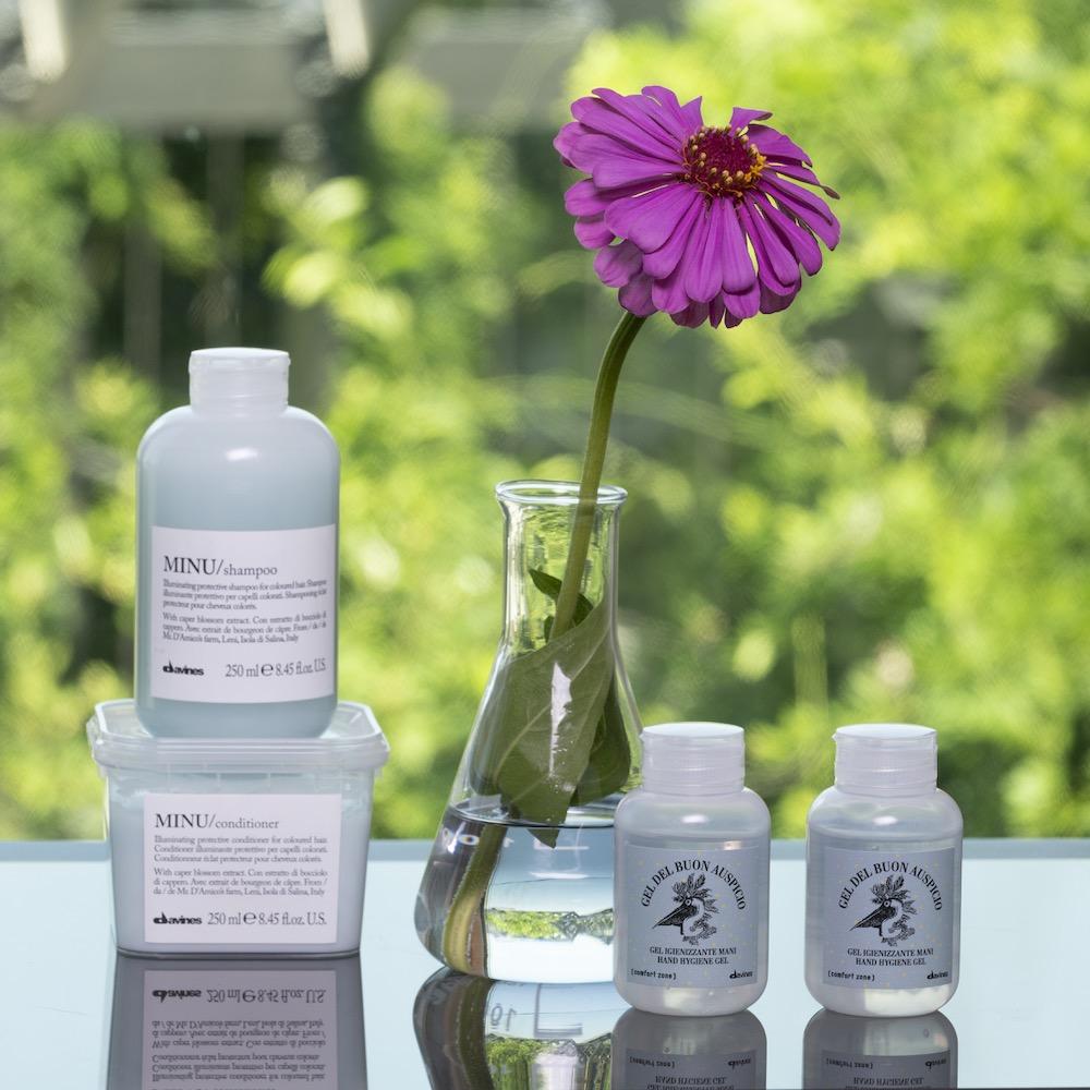 DAVINES-Produkte mit violetter Gerbera in einer Glasvase