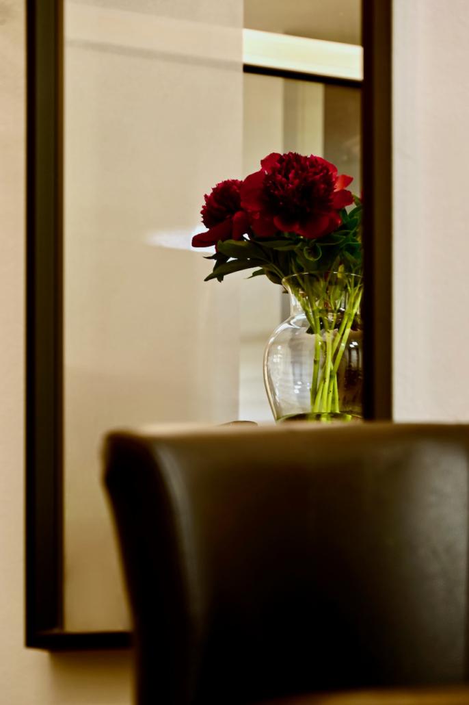 Salon mit Pfingstrosen durch einen Wandspiegel gesehen